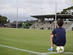 Boy sitting on a soccer ball looking over the CB Smith soccer oval