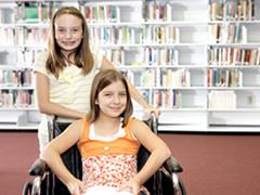 Girl in wheelchair with friend and library shelves in background.
