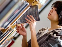 Girl putting a library book back on the shelf