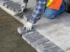 A construction work laying pavers next to a footpath.