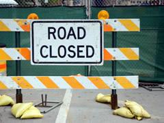 \'Road closed\' sign with a barrier and fencing.