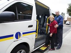 An older lady getting into the Health Appointment Transport Service Bus