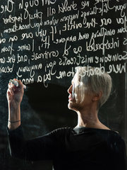 artist writing words on glass with white texta