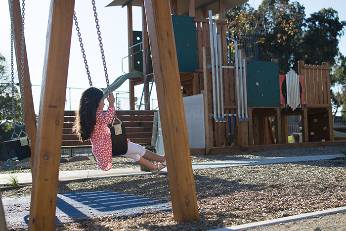 Young girl playing on the swing at Bush Reserve playground