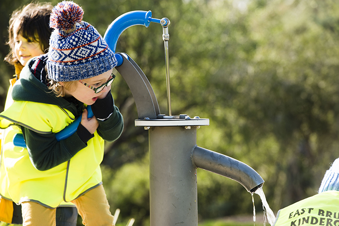 Children using the water pump at Kirkdale Park playspace